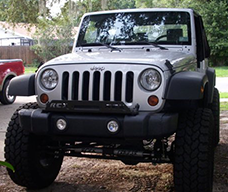silver JK Jeep with very large tires sitting in driveway
