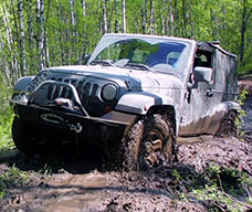 dirt covered jeep with after market parts insurance coverage going through mud in the woods