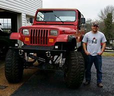 Man standing next to red jeep to show height difference in the vehicle lift